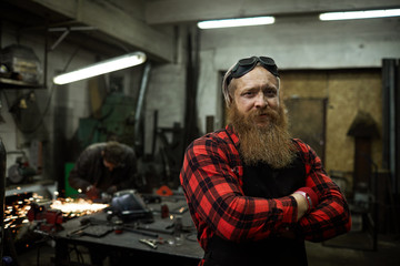 Content confident strong male blacksmith with long beard wearing safety goggles on head standing in welding shop and looking at camera