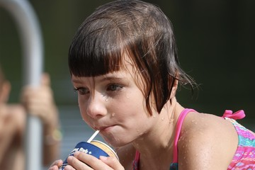 Wet young child having a drink while taking a break from swimming