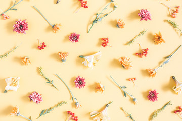 Autumn composition. Pattern made of orange and yellow flowers on pastel yellow background. Autumn, fall concept. Flat lay, top view
