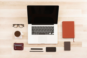 Top view laptop computer with phone, cup of black coffee, glasses, marker, pencil, diary, purse, hard drive on wooden background. Business template mock up. Minimal style. Flat lay, top view.