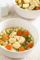 Homemade chicken soup with pea, carrot and small shell pasta in bowls, photographed with natural light (Selective Focus, Focus in the middle of the first soup)