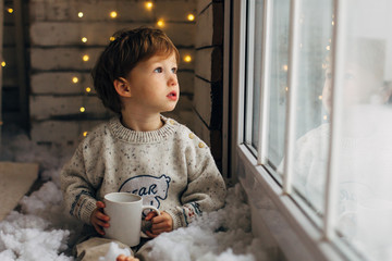 Little boy waiting for Santa Clause. Cute curly toddler boy sitting near the window