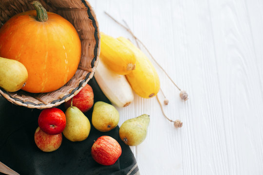 Hello autumn concept and Fall Harvest. Pumpkin and zucchini in stylish straw basket with apples and pears on white wooden background in light, Space for text. Happy Thanksgiving