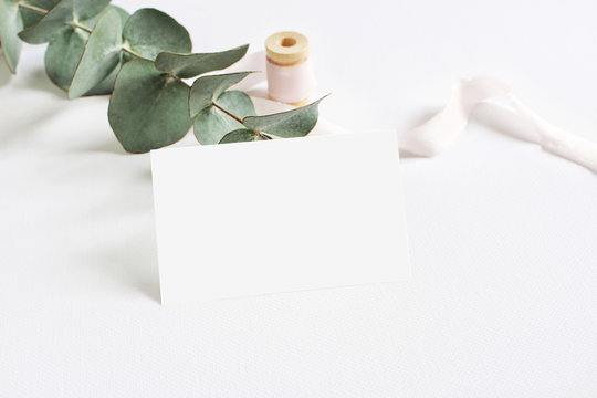 Feminine stationery mockup scene with a paper greeting card, spool of pink silk ribbon and Silver dollar eucalyptus leaves on a white table background. Wedding styled stock photography.