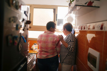 Cuban same-sex couple Onelia Miranda and Mercedes Garcia, who have been together for ten years, talk at the kitchen while preparing coffee at their apartment in Havana