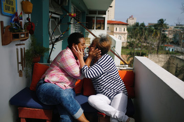 Cuban same-sex couple Mercedes Garcia and Onelia Miranda, who have been together for ten years, share a moment at the balcony of their apartment in Havana