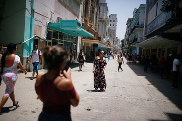 Cubans are seen at a commercial area in Havana
