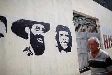 """A Cuban walks by graffiti of revolutionary heroes Camilo Cienfuegos and Ernesto """"Che"""" Guevara in Havana"""