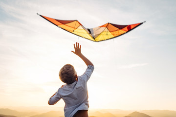 Boy start to fly bright orange kite in the sky Wall mural