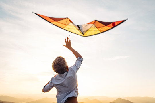 Boy start to fly bright orange kite in the sky