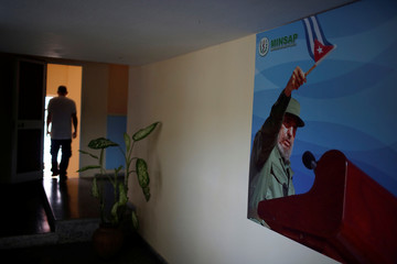 Man is silhouetted near a picture of Castro before the beginning of the public political discussion to revamp a Cold War-era constitution in Havana