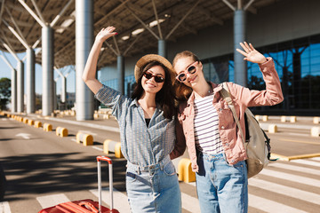 Two cute smiling girls in sunglasses happily looking in camera while raising hands up with suitcase and backpack on shoulder outdoor near airport