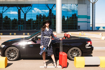 Beautiful girl in sunglasses and black hat holding on heels passport with flight ticket and red suitcase near airport with cabriolet on background