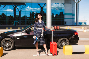 Pretty smiling girl in sunglasses and black hat holding on heels passport with flight ticket and red suitcase near airport with cabriolet on background