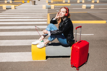 Pretty girl in headphones listening music dreamily closing eyes with tablet in hand and red suitcase near