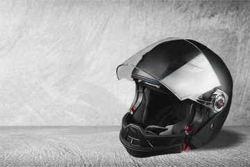 Black biker helmet on gray background