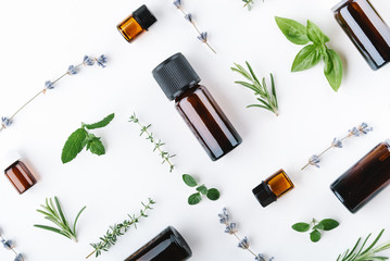 essential oils with botles and herbs on white background Fototapete