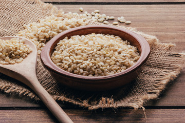 Full container with brown rice, rustic style