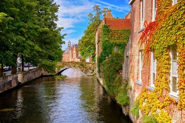 Bridge and leafy buildings lining the picturesque canals of Bruges, Belgium