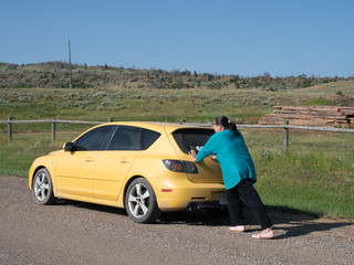 Hispanic Woman Pushing a Yellow Car That Has Run Out of Gas