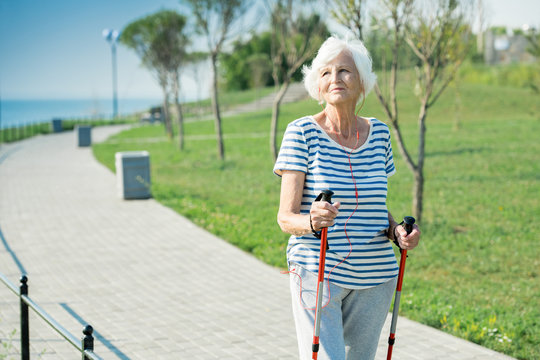 Portrait of active senior woman practicing Nordic walking with poles outdoors in park, copy space