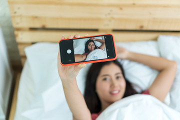 Attractive happy young woman taking selfie with smartphone in the morning on white bed. Focus hand holding mobile.