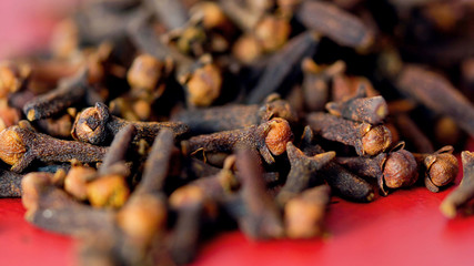 Cloves cooking spices macro closeup. on vintage red wood table, selective focus.
