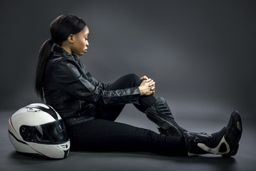 Black female wearing leather and helmet posing in a studio as a race car driver, motorcycle rider, or a stunt woman.  She is sitting down and looks fearless and adventurous.