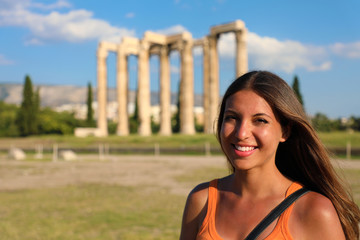 Smiling tourist woman with the greek temple of Olympian Zeus on the background, Athens, Greece