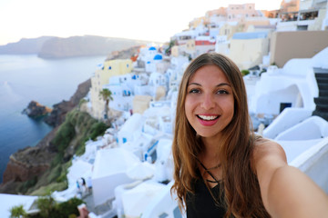 Self portrait of smiling girl in Oia village, Santorini. Cute happy tourist girl taking selfie picture during summer vacation in famous European destination Santorini, Greece.