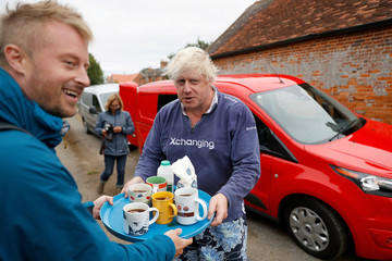 Britain's former Foreign Secretary Boris Johnson offers cups of tea to journalists outside his home near Thame in Oxfordshire