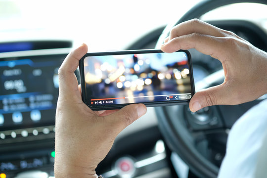 Close up of men's hands holding mobile phone while play video from network in parking lot