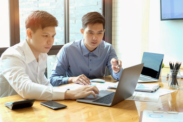 Two Asian businessmen working together in business meeting room in office