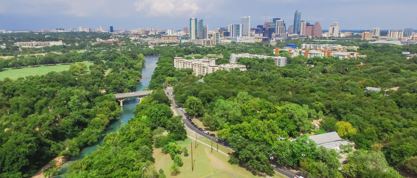 Panorama aerial view Downtown from Barton Creek in Greenbelt at Zilker Metropolitan Park south Austin with summer blue cloud sky. Located at eastern edge of Hill Country, is the state capital of Texas