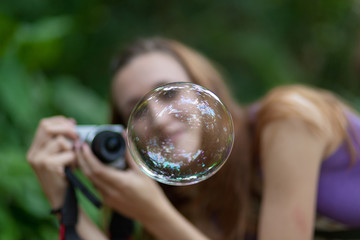 A girl tries to capture a soap bubble seen behind the soap bubble that reflects the trees above it