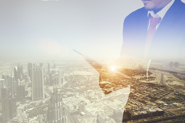 Double exposure of a businessman and a city using a tablet, cityascape and network concept
