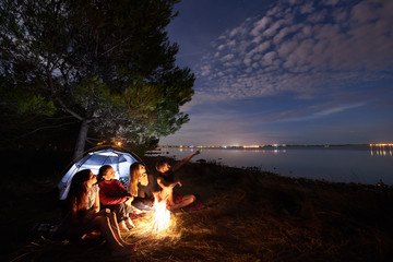 Group of four tourists resting on lake shore at campfire in front of tourist tent under tree, bearded man pointing at bright blue night sky on clear water background. Tourism and camping concept.