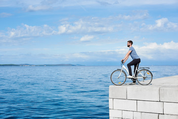 Young bearded man tourist on bicycle on high paved stone sidewalk enjoying clear blue sea water. Active holiday and tourism concept.