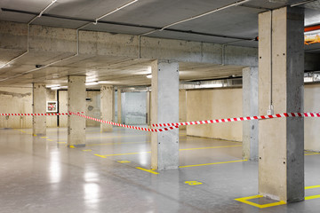 Renewed underground car parking with yellow lot marking and warning tape