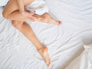 beautiful sexy young woman legs on the white sheets