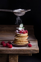 Pancakes with raspberries and berries around on black backgound