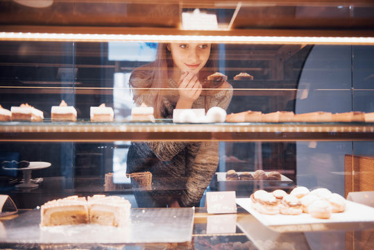 Smiling woman at camera through the showcase with sweet and cakes in modern cafe interior