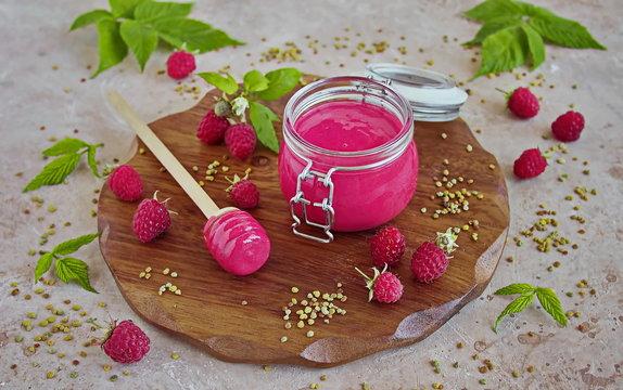 Homemade berry whipped honey with fresh raspberries in a glass jar, fresh raspberries on a wooden tray