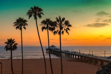 Palm trees and Pier on Manhattan Beach at sunset in California, Los Angeles, USA. Vintage processed.