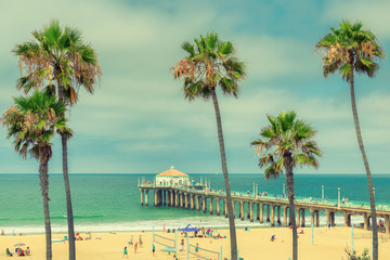 Palm trees on Manhattan Beach and pier in Los Angeles, California. Vintage processed. Fashion travel and tropical beach concept.  Wall mural