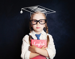Smart child girl student with education book and graduation hat on blackboard background, learning english concept