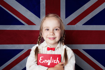 English concept with little girl student with book against the UK flag background. Learn english...