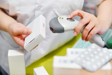 Fototapeta Pharmacist scanning barcode of medicine drug in a pharmacy drugstore. obraz
