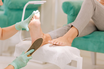 Female chiropodist. Professional skillful female chiropodist working hard in her beauty salon providing good service