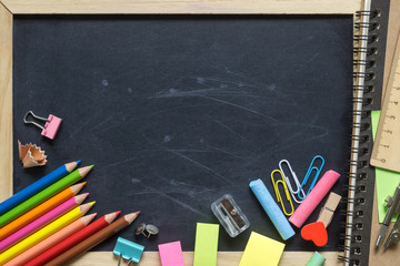 Empty Blank Black Chalk board Background with wooden frame and School supplies, ideal for back to school and education background.